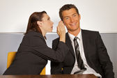 Businesswoman whispering in businessman — Stock Photo