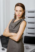 Portrait of businesswoman with arms crossed at office — Stock Photo