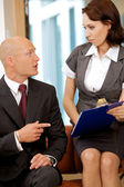 Young confident boss and his secretary looking on documents — Stockfoto
