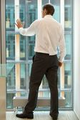 Young caucassian businessman standing against office window — Stock Photo