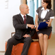 Young confident boss and his secretary looking on documents — Stock Photo