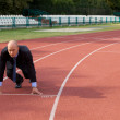 Businessman at the start line of running track — Foto Stock