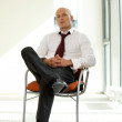 Young confident caucasian businessman sitting on office chair — Stock Photo