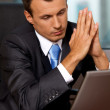 Stock Photo: Businessmusing laptop with hands clasped in office