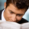 Businessman reading newspaper in office — Stock Photo