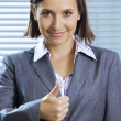 Portrait of smiling businesswoman showing thumbs up - Stock Photo