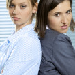 Portrait of businesswomen standing back to back in office — Stock Photo