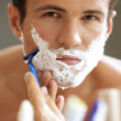 Stock Photo: Portrait of young man shaving