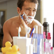 Reflection of young man shaving in mirror - Stock Photo