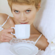 Woman drinking caffee in bed - Stock Photo