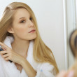 Woman brushing hair — Stockfoto