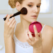 A woman applying make-up — Stock Photo