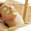 Young woman lying down on massage table with cucumbers on eyes and face — ストック写真
