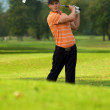Young man swinging golf club - Stockfoto