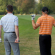 Young men standing in golf course with sticks, rear view - Stock Photo