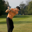 Young man swinging golf club — Stok fotoğraf