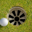 Close-up of golf ball near hole — Stock Photo