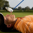 Man balancing golf ball on tee in his mouth — Stock Photo