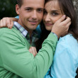 Portrait of young couple posing together by tree — Stock Photo