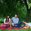 Man pouring wine to glass sitting next to girlfriend in park — Stock Photo #3814217