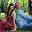Young couple sitting back to back in park — Stock Photo