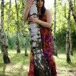 portrait of young woman hugging baum im park — Stockfoto