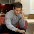 Young man on the phone, using laptop — Stockfoto