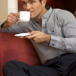 Young man drinking tea, sitting in sofa — Stock Photo #3814377