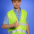Portrait of architect in coveralls and hardhat showing thumbs up sign — Stock Photo #3814434