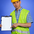 Portrait of architect in coveralls and hardhat pointing at clipboard — Stock Photo #3814449