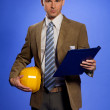 Portrait of businessman holding hardhat and clipboard — Stock Photo