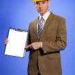Portrait of businessman in hardhat pointing at clipboard — Stock Photo #3814470