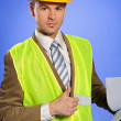 Portrait of businessman in coveralls holding clipboard and showing thumbs up sign — Stock Photo #3814476
