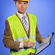Portrait of businessman in coveralls writing on clipboard — Stockfoto