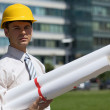 Stock Photo: Portrait of architect in hardhat holding blueprint at construction site