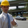 Royalty-Free Stock Photo: Portrait of architect in hardhat showing thumbs up sign at construction sit