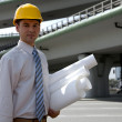 Portrait of architect in hardhat holding blueprint at construction site — Stock Photo #3814540