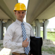 Portrait of architect in hardhat holding laptop bag and showing thumbs up sign — Stock Photo