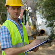 Portrait of architect using clipboard at construction site — Stock Photo