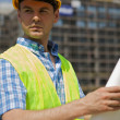 Engineer holding blueprint at construction site — Stock Photo