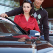 Portrait of young couple standing by new car — Stock Photo