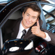 Portrait of man sitting in new car showing thumbs up — Stock Photo #3814766