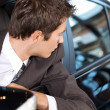 Young man sitting in new car — Stock Photo