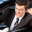 Angry young man clenching his fist, sitting in new car — Stock Photo #3814777