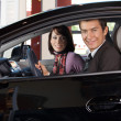 Portrait of young couple sitting in a new car at showroom — Stock Photo