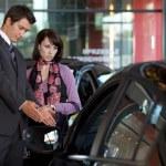 Car salesman explaining car features to customer — Stock Photo #3814815