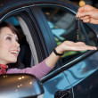 Young woman receiving the car keys from car salesman — Stock Photo