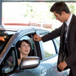 Car salesman conversing with female customer, sitting in new car — Stock Photo