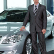Stock Photo: Portrait of car salesperson standing in car showroom