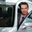 Stock Photo: Car salesperson getting in car at showroom